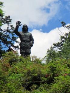 小山の上に立つヤマトタケルのブロンズ像